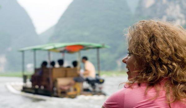 Туристка, подорожуюча на човні по річці в Китаї
