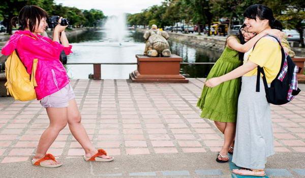 Туристки позують на тлі місцевих пам'яток, Китай