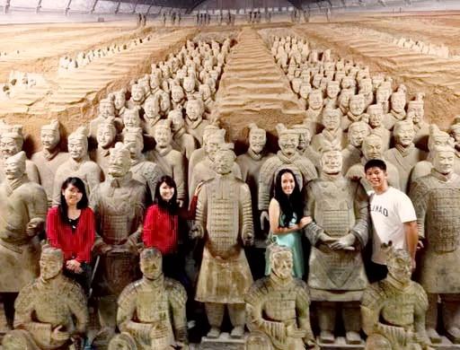 Люди поряд із скульптурами теракотових воїнів